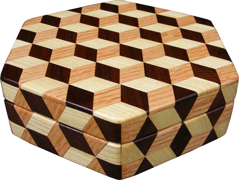 """Medium Hexagon Tumbling Block Box, view 2<br /> The medium hexagon box Tumbling Block is based on the """"Tumbling Block"""" quilt pattern. It measures 7 ¼"""" X 8 3/8"""" and 2 3/8"""" high. Inside measurements are 6 ¼"""" X 7"""" X 1 ½"""".  There are 198 pieces on the overlay. The pieces are cut and glued in place, one piece at a time. The pattern covers the top and extends over the edge uninterrupted, to the bottom. The box is finished in its natural color with 5 or 6 coats of a clear wiping varnish, rubbed in by hand. The pieces are a bit over 3/16"""" thick, glued onto a Baltic Birch base.<br /> <br /> This box is made from Hackberry, Oak, and Walnut, all native to Missouri. I lined the box with black velveteen.<br /> <br /> The pattern has the illusion of a lot of blocks but there are as many stars as there are blocks. The design forces you to see the blocks. On each diamond, if you go to the side you are in the middle of a block. At each point you are in the middle of a star that has 6 points."""
