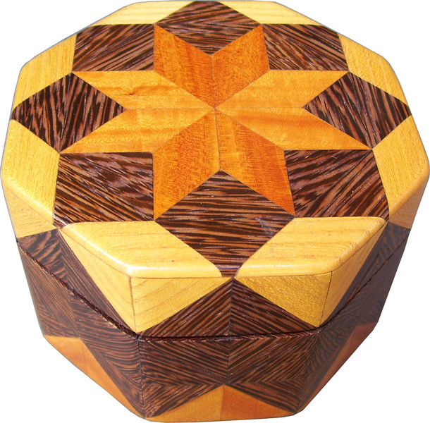 """Oct Box Sw-Wenge-Hb<br />  This Octagon Box measures 5"""" x 5"""" and is 3 ¼"""" tall.  There are 128 pieces on the box in the diamond and triangle shape.  The box is finished in its natural color with 5 or 6 coats of a clear wiping varnish rubbed in by hand.  The pieces are a bit over 3/16"""" thick glued onto a birch plywood base.  The type of wood is listed on the bottom of the box from the center out.  On this box is """"Satinwood"""" from Sri Lanka (a very pretty wood), """"Wenge"""" from West Africa and """"Hackberry"""" from Missouri. Some of the Wenge on this box has what I call a """"lightning strike"""" look, as the grain is jagged, a very nice effect.   It is lined with black velvet."""