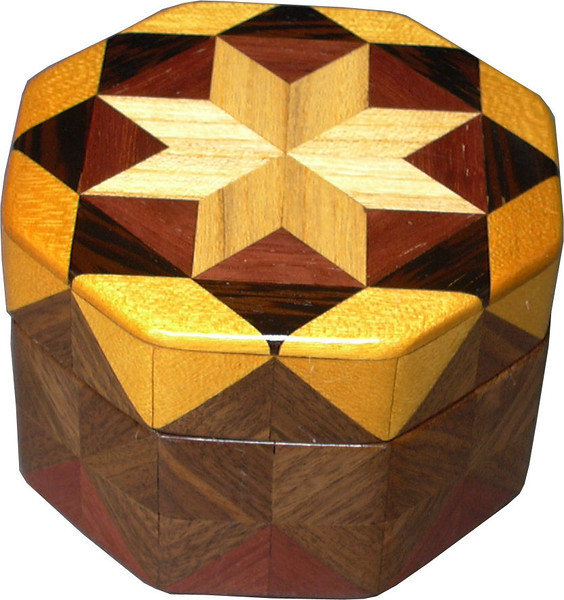 """Oct Box Bright  <br /> This Octagon Box measures 5"""" x 5"""" and is 3 ¼"""" tall.  There are 128 pieces on the box in the diamond and triangle shape.  The box is finished in its natural color with 5 or 6 coats of a clear wiping varnish rubbed in by hand.  The pieces are a bit over 3/16"""" thick glued onto a Baltic Birch base.  The type of wood is listed on the bottom of the box from the center out.  On this box is """"Hackberry"""" from Missouri, """"Purpleheart"""" from Central or South America, """"Wenge"""" from West Africa, """"Satinwood"""" from South America and """"Walnut"""" from Missouri.<br /> <br />     I made this box in 1998.  On the bottom I signed it, listed the wood, and dated it.  After the date, the words """"Foot Cut"""" let you know I made it on a foot powered table saw.<br /> <br />     It is lined with black velveteen."""
