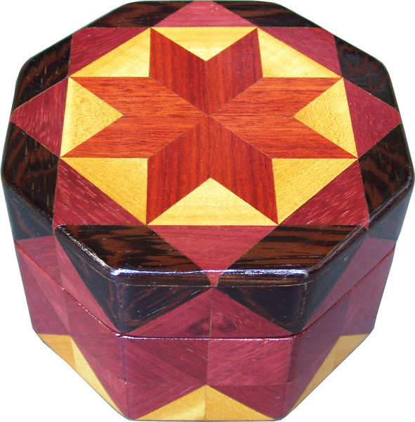 """Oct Box Bloodwood Star<br />  This Octagon Box measures 5"""" x 5"""" and is 3 ¼"""" tall.  There are 128 pieces on the box in the diamond and triangle shape.  The box is finished in its natural color with 5 or 6 coats of a clear wiping varnish rubbed in by hand.  The pieces are a bit over 3/16"""" thick glued onto a Baltic Birch base.  The type of wood is listed on the bottom of the box from the center out.  On this box is """"Bloodwood"""" from South America, """"Satinwood"""" from Sri Lanka, """"Purpleheart"""" from Central or South America and """"Wenge"""" from West Africa.   It is lined with black velveteen."""