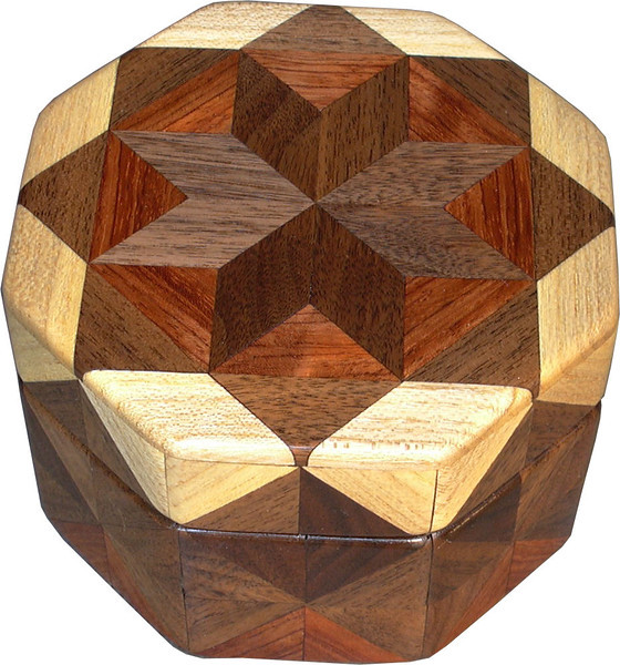 """Oct Box Wal-Bub-HB<br />   This Octagon Box measures 5"""" x 5"""" and is 3 ¼"""" tall.  There are 128 pieces on the box in the diamond and triangle shape.  The box is finished in its natural color with 5 or 6 coats of a clear wiping varnish rubbed in by hand.  The pieces are a bit over 3/16"""" thick glued onto a birch plywood base.  The type of wood is listed on the bottom of the box from the center out.  On this box is """"Walnut from Missouri, """"Bubinga"""" from Africa and """"Hackberry"""" from Missouri.  It is lined with rust colored velveteen."""
