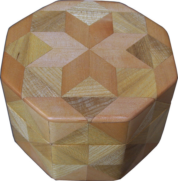 "Oct Box Birch-Hb<br />  This Octagon Box measures 5"" x 5"" and is 3 ¼"" tall.  There are 128 pieces on the box in the diamond and triangle shape.  The box is finished in its natural color with 5 or 6 coats of a clear wiping varnish rubbed in by hand.  The pieces are a bit over 3/16"" thick glued onto a birch plywood base.  The type of wood is listed on the bottom of the box from the center out.  On this box is ""Birch"" and ""Hackberry"" from Missouri.  It is lined with black velveteen."