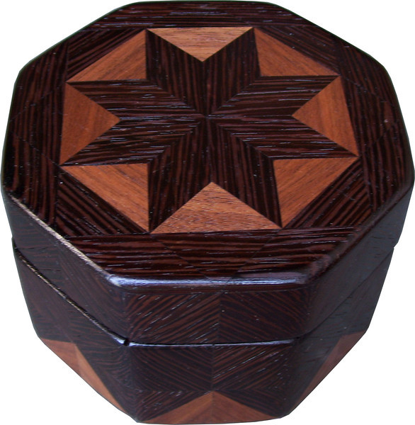 """Oct Box Wenge-Wal<br />   This Octagon Box measures 5"""" x 5"""" and is 3 ¼"""" tall.  There are 128 pieces on the box in the diamond and triangle shape.  The box is finished in its natural color with 5 or 6 coats of a clear wiping varnish rubbed in by hand.  The pieces are a bit over 3/16"""" thick glued onto a birch plywood base.  The type of wood is listed on the bottom of the box from the center out.  On this box is """"Wenge"""" from West Africa and """"Walnut"""" from Missouri.  It is lined with black velveteen."""