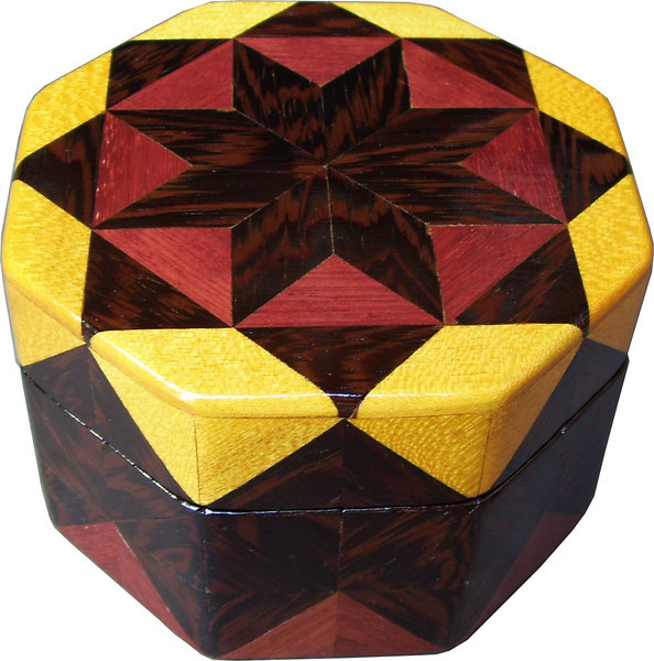 """Oct Box Wenge Star<br />  This Octagon Box measures 5"""" x 5"""" and is 3 ¼"""" tall.  There are 128 pieces on the box in the diamond and triangle shape.  The box is finished in its natural color with 5 or 6 coats of a clear wiping varnish rubbed in by hand.  The pieces are a bit over 3/16"""" thick glued onto a Baltic Birch base.  The type of wood is listed on the bottom of the box from the center out.  On this box is """"Wenge"""" from West Africa, """"Purpleheart"""" and """"Satinwood"""" from Central or South America. It is lined with black velveteen."""