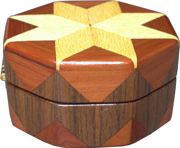 """Hb-Cedar-Wal Ring Box<br />  This is my """"Hackberry, Cedar and Walnut"""" Ring Box.  It measures 3 1/2"""" x 3 1/2"""" and is 2"""" high.  There are 56 pieces on this box.  The pieces are all the """"full size"""" diamonds and triangles, except for the 16 half size triangles around the bottom.  It is finished in its natural color with 5 or 6 coats of clear wiping varnish rubbed in by hand.  The pieces are a bit over 3/16"""" thick, glued onto a Baltic Birch base.  So hold up much better than a thin veneer.  <br /> <br />   The type of wood is listed on the bottom of the box, from the center out.  On this box is """"Hackberry, Cedar and Walnut"""" from Missouri.  <br /> <br />   I made this box in 1997.  On the bottom I signed it, listed the wood, and dated it.  After the date the words """"Foot Cut"""" let you know I made it on a foot powered table saw.  My brother helped me make the saw around 1992.  <br /> <br />   The inside is lined with black velveteen.   It has 3 """"ring pads"""" on the bottom forming 2 slots about 2 ½"""" long, for rings."""
