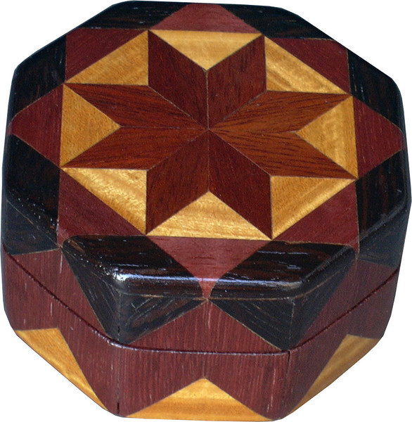 "Bloodwood Star Ring Box<br />  This is my ""Bloodwood Star"" Ring Box.  It measures 3 1/2"" x 3 1/2"" and is 2"" high.  There are 72 pieces, both full and half size diamonds and triangles, on this box.  On the top there are 32 half size pieces where it would normally have 16 full size pieces.  It is finished in its natural color with 5 or 6 coats of clear wiping varnish, rubbed in by hand.  The pieces are a bit over 3/16"" thick, glued onto a Baltic Birch base.  <br /> <br />     The type of wood is listed on the bottom of the box from the center out.  On this box is ""Bloodwood"" from South America, ""Satinwood"" from Sri Lanka, ""Purpleheart"" from Central or South America and ""Wenge"" from West Africa.  <br /> <br />     I made this box in 1996.  On the bottom I signed it, listed the wood, and dated it.  After the date, the words ""Foot Cut"" let you know I made it on a foot powered table saw.<br /> <br />     It is lined with black velveteen.  It has 3 ""ring pads"" on the bottom forming 2 slots about 2 ½"" long, for rings."