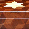 "Small Walnut Hexagon Box, view 1<br /> The Small Walnut Hexagon Box is based on the ""Tumbling Block"" quilt pattern except that it is all walnut but for the six pointed star. It measures 4 3/8"" X 8 3/8"" and 2 3/8"" high. Inside measurements are 3 ¼"" X 7"" X 1 ½"".  There are 148 pieces on the overlay. The pieces are cut and glued in place, one piece at a time. The pattern covers the top and extends over the edge uninterrupted, to the bottom. The box is finished in its natural color with 5 or 6 coats of a clear wiping varnish, rubbed in by hand. The pieces are a bit over 3/16"" thick, glued onto a Baltic Birch base<br /> <br /> This box is made from Hackberry, and Walnut, both native to Missouri. I lined the box with black velveteen."