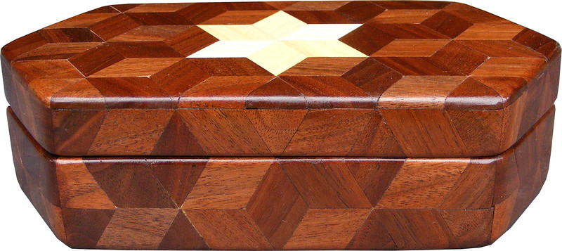 """Small Walnut Hexagon Box, view 1<br /> The Small Walnut Hexagon Box is based on the """"Tumbling Block"""" quilt pattern except that it is all walnut but for the six pointed star. It measures 4 3/8"""" X 8 3/8"""" and 2 3/8"""" high. Inside measurements are 3 ¼"""" X 7"""" X 1 ½"""".  There are 148 pieces on the overlay. The pieces are cut and glued in place, one piece at a time. The pattern covers the top and extends over the edge uninterrupted, to the bottom. The box is finished in its natural color with 5 or 6 coats of a clear wiping varnish, rubbed in by hand. The pieces are a bit over 3/16"""" thick, glued onto a Baltic Birch base<br /> <br /> This box is made from Hackberry, and Walnut, both native to Missouri. I lined the box with black velveteen."""
