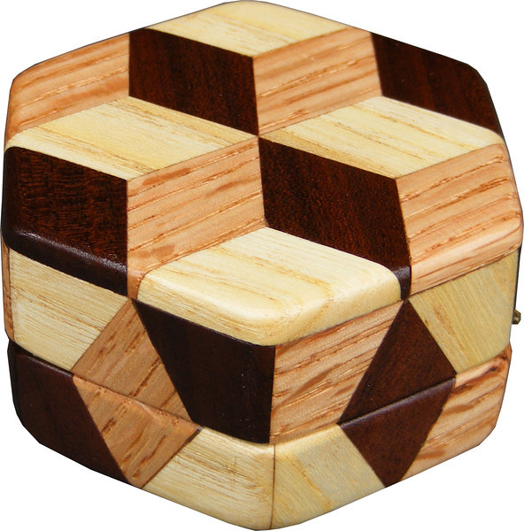 """Tiny Hexagon Tumbling Block Box, view 2<br /> The Tiny Hexagon Tumbling Block Box is based on the """"Tumbling Block"""" quilt pattern. It measures 2 7/8"""" X 3 1/4"""" and 1 5/8"""" high. Inside measurements are 2"""" X 2 1/8"""" X 3/4"""".  There are 42 pieces on the overlay. The pieces are cut and glued in place, one piece at a time. The pattern covers the top and extends over the edge uninterrupted, to the bottom. The box is finished in its natural color with 5 or 6 coats of a clear wiping varnish, rubbed in by hand. The pieces are a bit over 3/16"""" thick, glued onto a Baltic Birch base.<br /> <br /> This box is made from Hackberry, Oak, and Walnut, all native to Missouri. I lined the box with black velveteen.<br /> <br /> The pattern has the illusion of a lot of blocks but there are as many stars as there are blocks. The design forces you to see the blocks. On each diamond, if you go to the side you are in the middle of a block. At each point you are in the middle of a star that has 6 points."""