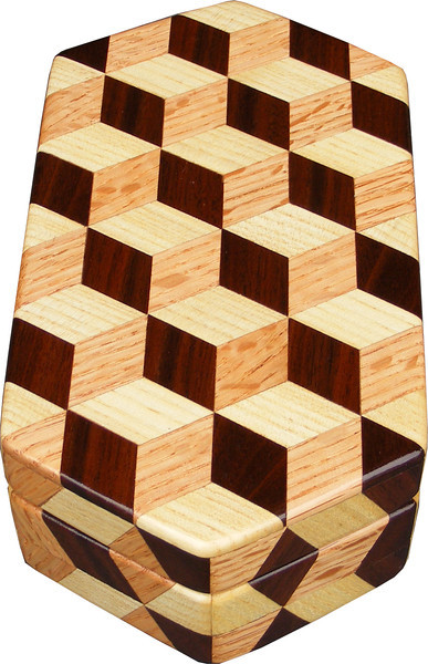 """Small Hexagon Tumbling Block Box, view 2<br /> I am not real pleased with how I have to bring the design over the sides on the front and back corners. The two ends are fine where I have a diamond on the top. But where I have two triangles, I can't bring the design over onto the sides like I like to as you can see on the other Tumbling Block boxes, or on the ends of this one.<br /> <br /> The Small Hexagon Tumbling Block Box is based on the """"Tumbling Block"""" quilt pattern. It measures 4 3/8"""" X 8 3/8"""" and 2 3/8"""" high. Inside measurements are 3 ¼"""" X 7"""" X 1 ½"""".  There are 148 pieces on the overlay. The pieces are cut and glued in place, one piece at a time. The pattern covers the top and extends over the edge uninterrupted, to the bottom. The box is finished in its natural color with 5 or 6 coats of a clear wiping varnish, rubbed in by hand. The pieces are a bit over 3/16"""" thick, glued onto a Baltic Birch base<br /> <br /> This box is made from Hackberry, Oak, and Walnut, all native to Missouri. I lined the box with black velveteen.<br /> <br /> The pattern has the illusion of a lot of blocks but there are as many stars as there are blocks. The design forces you to see the blocks. On each diamond, if you go to the side you are in the middle of a block. At each point you are in the middle of a star that has 6 points."""