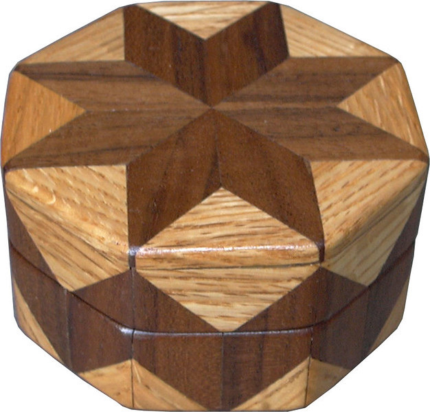 "Walnut & Oak Ring Box<br />  This is my ""Walnut"" and ""Oak"" Ring Box.  It measures 3 1/2"" x 3 1/2"" and is 2"" high.  There are 56 pieces on this box.  The pieces are all the ""full size"" diamonds and triangles, except for the 16 half size triangles around the bottom.  It is finished in its natural color with 5 or 6 coats of clear wiping varnish rubbed in by hand.  The pieces are a bit over 3/16"" thick, glued onto a Baltic Birch base, so   they hold up much better than a thin veneer.  <br /> <br />   The type of wood is listed on the bottom of the box, from the center out.  On this box is ""Walnut"", and ""Oak"" from Missouri.  <br /> <br />   On the bottom I signed it, listed the wood, and dated it.  After the date, the words ""Foot Cut"" let you know I made it on a foot powered table saw.  My brother helped me make the saw around 1992.  <br /> <br />   The inside is lined with black velveteen.   It has 3 ""ring pads"" on the bottom forming 2 slots about 2 ½"" long, for rings."