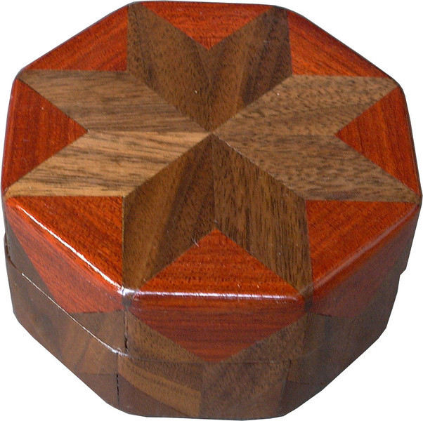 """Walnut & Bloodwood Ring Box<br />    This is my """"Walnut and Bloodwood"""" Ring Box.  It measures 3 1/2"""" x 3 1/2"""" and is 2"""" high.  There are 56 pieces on this box.  The pieces are all the """"full size"""" diamonds and triangles, except for the 16 half size triangles around the bottom.  It is finished in its natural color with 5 or 6 coats of clear wiping varnish rubbed in by hand.  The pieces are a bit over 3/16"""" thick, glued onto a Baltic Birch base.  So they hold up much better than a thin veneer.  <br /> <br />     The type of wood is listed on the bottom of the box, from the center out.  On this box is """"Walnut"""" from Missouri and """"Bloodwood"""" from South America.  <br /> <br />       On the bottom I signed it, listed the wood, and dated it.  After the date the words """"Foot Cut"""" let you know I made it on a foot powered table saw.  My brother helped me make the saw around 1992.  <br /> <br />     The inside is lined with black velveteen.   It has 3 """"ring pads"""" on the bottom forming 2 slots about 2 ½"""" long, for rings."""