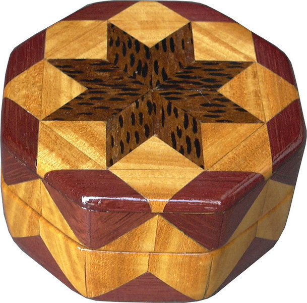 """Bp-Sw-Ph Ring Box<br />  This is my """"Black Palm, Satinwood and Purpleheart"""" Ring Box.  It measures 3 1/2"""" x 3 1/2"""" and is 2"""" high.  There are 72 pieces, both full and half size diamonds and triangles, on this box.  On the top there are 32 half-size pieces where it would normally have 16 full size pieces.  It is finished in its natural color with 1 coat of varnish brushed on and 3 coats of clear wiping varnish, rubbed in by hand.  The pieces are a bit over 3/16"""" thick, glued onto a Baltic Birch base.  <br /> <br />   The type of wood is listed on the bottom of the box from the center out.  On this box is """"Black Palm"""" from Indonesia. (I cut this wood at an angle to give the black dots a different look.) """"Satinwood"""" from Sri Lanka is a wood with a beautiful golden satiny luster to it. Then """"Purpleheart"""" from Central or South America which is a very bright purple wood. <br /> <br />    This box is all made from very exotic wood.  <br /> <br />   I made this box in 2004.  On the bottom I signed it, listed the wood, and dated it.  After the date, the words """"Foot Cut"""" let you know I made it on a foot powered table saw.<br /> <br />   It is lined with black velveteen.  It has 3 """"ring pads"""" on the bottom forming 2 slots about 2 ½"""" long, for rings."""