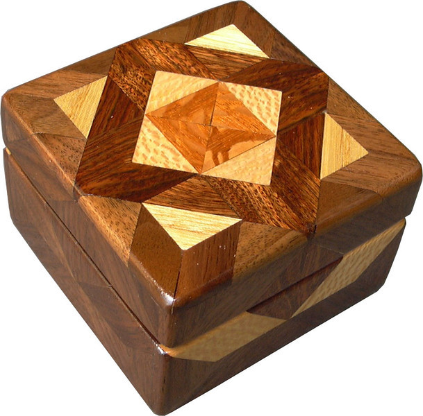 """Tiny Sq Brown Tone Box<br />  I call this my """"Tiny Square Brown Tone"""" Box. On the top of the box is an """"Aunt Sukeys Choice"""" quilt pattern.  The square box is about 3 1/2"""" x 3 1/2"""" and 2 1/2"""" tall. Inside it is 2 1/2"""" x 2 1/2"""" x 1 1/2"""".  I made it using 92 pieces of wood cut in either diamond or triangle shapes from different kinds of wood. I used the half size pieces for the """"Aunt Sukeys Choice"""" pattern on the top, so there are 40 pieces where I would normally have 20 pieces. The box is finished in its natural color with 5 or 6 coats of a clear wiping varnish, rubbed in by hand. The pieces are a bit over 3/16"""" thick, glued onto a Baltic Birch base, so they hold up much better than a thin veneer.<br />    The type of wood is listed on the bottom of the box from the center out. On this box the wood is """"Lacewood"""" from Australia, """"Sycamore"""" from Missouri, """"Chechen"""" from Mexico, """"Hackberry"""" and """"Walnut"""" from Missouri.<br />      On the bottom I signed it, listed the wood, and dated it.  After the date, the words """"Foot Cut"""" let you know I made it on a foot powered table saw.<br /> <br />    I lined the box with black velveteen."""