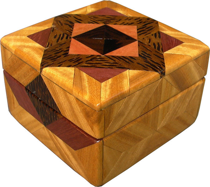 """Tiny Sq Sw-Ph Box<br /> All the natural colors of the different kinds of wood.<br /> <br />  I call this my """"Tiny Square Satinwood and Purpleheart"""" Box. On the top of the box is an Aunt Sukeys Choice quilt pattern. The square box is about 3 1/2"""" x 3 1/2"""" and 2 1/2"""" tall. Inside it is 2 1/2"""" x 2 1/2"""" x 1 1/2"""". I made it using 92 pieces of wood cut in either diamond or triangle shapes from different kinds of wood. I used the half size pieces for the """"Aunt Sukeys choice"""" pattern on the top, so there are 40 pieces where I would normally have 20 pieces. The box is finished in its natural color with 1 coat of varnish brushed on and 3 coats of a clear wiping varnish, rubbed in by hand. The pieces are a bit over 3/16"""" thick, glued onto a Baltic Birch base, so they hold up much better than a thin veneer.<br />  The type of wood is listed on the bottom of the box from the center out. On this box the wood is """"Ziricote"""" from South America, """"Pink Ivory"""" from South Africa (a wood that is sacred to the Zulu tribe). """"Black Palm"""" from Indonesia. (I cut this on an angle to give the black dots a different look) """"Purpleheart"""" from Central or South America is a very bright purple wood. Then """"Satinwood"""" from Sri Lanka is used on the main part of the box. Satinwood has the most beautiful golden satiny luster to it. <br /> I made this box in 2004. On the bottom I signed it, listed the wood, and dated it. After the date, the words """"Foot Cut"""" let you know I made it on a foot powered table saw."""