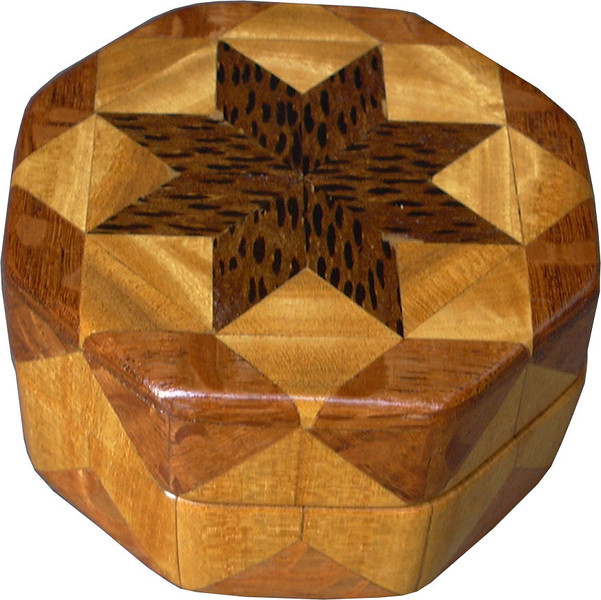 """Bp-Sw-Lw Ring Box<br />   This is my """"Black Palm, Satinwood and Lacewood"""" Ring Box.  It measures 3 1/2"""" x 3 1/2"""" and is 2"""" high.  There are 72 pieces, both full and half size diamonds and triangles, on this box.  On the top there are 32 half-size pieces where it would normally have 16 full size pieces.  It is finished in its natural color with 1 coat of varnish brushed on and 3 coats of clear wiping varnish, rubbed in by hand.  The pieces are a bit over 3/16"""" thick, glued onto a Baltic Birch base.  <br /> <br />   The type of wood is listed on the bottom of the box from the center out.  On this box is """"Black Palm"""" from Indonesia. (I cut this wood at an angle to give the black dots a different look.) """"Satinwood"""" from Sri Lanka is a wood with a beautiful golden satiny luster to it. Then """"Lacewood"""" from Australia is a wood that has a nice coppery sheen to it. <br /> <br />    This box is all made from very exotic wood.  <br /> <br />   I made this box in 2004.  On the bottom I signed it, listed the wood, and dated it.  After the date, the words """"Foot Cut"""" let you know I made it on a foot powered table saw.<br /> <br />   It is lined with black velveteen.  It has 3 """"ring pads"""" on the bottom forming 2 slots about 2 ½"""" long, for rings."""