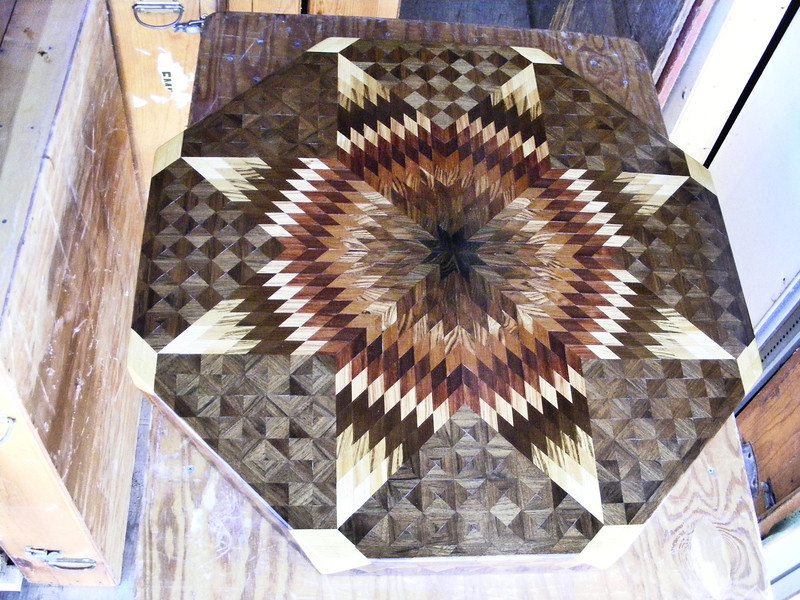 "Medium Walnut Star Coffee Table #2, view 2<br /> Probably 15 years ago I put 4 medium star tables out in a shed and haven't looked at them since. A couple things have happened lately to make me think that I should get a picture of at least the top of the tables. This second medium star table that I made is 32"" across and 19"" high when the pedestal is attached to it. It has 16 kinds of wood on it and over 2900 pieces of wood including what is on the pedestal and feet. They have held up very well in the boxes that I had them stored in considering the hot and cold that they have been in over the years.<br /> <br /> One thing I don't like about these tables is that back then I was using Elmer's glue to mix with sawdust to fill the small cracks between the pieces. Then in damp weather the glue joint rises and you can then feel a little ridge between each piece. It makes the whole top feel not as smooth as I like them to feel.<br /> <br /> The types of wood from the center are: Wenge, East India Rosewood, Brazilian Rosewood, Honduras Rosewood, Kingwood, Brazilwood, Bloodwood, Bubinga, Tulipwood, Canarywood, Narra, Zebrawood, Satinwood, Oak, Ash and Walnut."