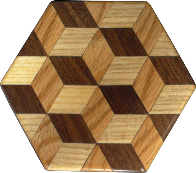 """Tumbling Block Trivet 2<br />   This is a """"Tumbling Block"""" quilt pattern trivet. It is made using diamonds and triangles from different kinds of wood, all in their natural colors. There are 30 pieces on this block, 24 diamonds and 6 triangles, all full size. There are as many stars as blocks. At the side of each diamond is the middle of a block. At the point of each diamond is the middle of a star with 6 points. It measures 4 ½"""" across. To finish them, I use 5 or 6 coats of a clear wiping varnish, rubbed in by hand.<br />  <br />   The type of wood is listed on the bottom from the center out. On this quilt block the wood is """"Hackberry"""", """"Oak"""", and """"Walnut"""" from Missouri.<br />  <br />    On the bottom I signed it, listed the wood, and dated it.  After the date, the words """"Foot Cut"""" let you know I made it on a foot powered table saw.<br /> <br />   The five pictures show the different look the one trivet can have as you lay it down different ways."""