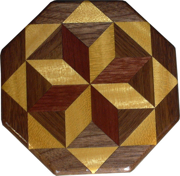 "Satinwood – Purpleheart and Walnut Trivet<br /> This is a quilt block decorative trivet or coaster. If used as a trivet I would not take a pan right off the stove and set it on it. Pour the contents into a dish and then set the dish on the trivet. It can withstand some water but it would be best not to let water stand on it very long. It is made using diamonds and triangles from different kinds of wood, all in their natural colors. There are 16 pieces on this block, 8 diamonds and 8 triangles, all full size. It measures 3 1/2"" across. To finish them, I use 1 coat of full strength varnish brushed on, and 3 coats of wiping varnish rubbed in by hand. <br /> <br />   The type of wood is listed on the bottom from the center out. On this quilt block the wood is ""Satinwood"" from Brazil (a very pretty yellow wood), ""Purple Heart"" from Central or South America (a very bright purple wood) and ""Walnut"" from Missouri.<br /> <br />    On the bottom I signed it, listed the wood, and dated it.  After the date, the words ""Foot Cut"" let you know I made it on a foot powered table saw."