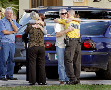Friends, family, and fellow police officers gather at the home of one of the slain officers Roger Castillo.  Two Miami-Dade police officers were shot dead while attempting to serve a homicide warrant. The officers were identified as Roger Castillo, father of three, and Amanda Haworth, also a mother.