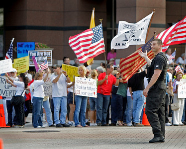 """Citizens held a Boston-inspired """"tea party"""" to protest government bailouts in front of the Federal Counthouse in Ft. Lauderdale.  A Ft. Lauderdale Police officer controls traffic on Broward Blvd. and cracks a smile during the process to another officer."""