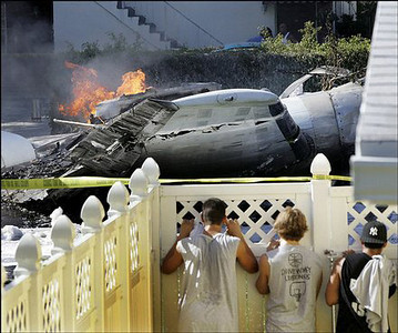 Neighborhood children watch a DC-9 cargo plane burn outside the front yard as they peek through a fence in Fort Lauderdale, Florida. The plane crashed and burned Monday in the middle of a street in a residential neighborhood. All three men aboard the plane survived, and there were no reports of injuries on the ground.