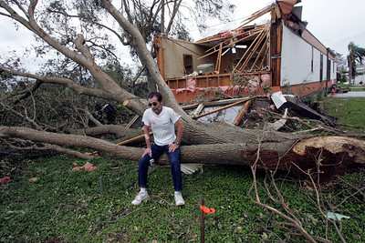 Village Park in Ft. Lauderdale is a moble home park that was hit hard with hurricane damage.  Resident Steve Ulise counts his blessings as he sits on the tree trunk that came thru his bedroom wall.  Steve was sleeping in bed when the tree just missed him.