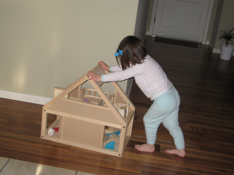 pushing her doll house back to her room