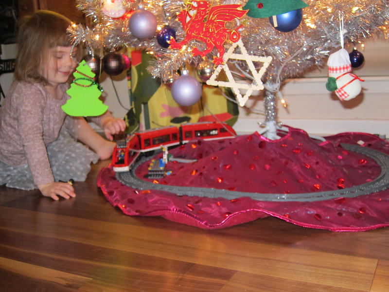 Etta playing with the Lego Train under the tree