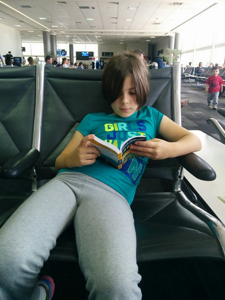 Brushing up on her French while we wait for the flight.
