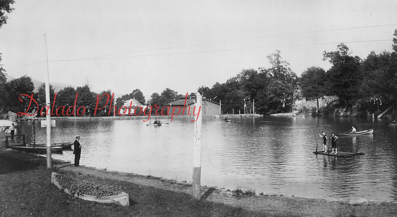 A view of the lake at Edgewood Park. The lake was formed from Furnace Run, which flows towards Shamokin. At center-right in this photo is a home-made diving board with four men on it. The white house in the center of this photo is possibly a home that once sat on Jackson Street. This photo is looking towards Shamokin. (This is now the bottom parking lot of Kemp Memorial Stadium.)