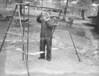 Elwood Spotts installs a swing. (May 19, 1955)