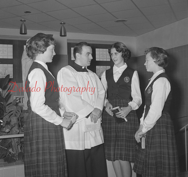 (Jan. 1960) Rev. Fred Farace, assistant pastor at St. Peter's Church, Mount Carmel, who served as a director during a retreat at Our Lady of Lourdes, talks to students. The girls took part in the period of presentations and conferences, while the young men paused for spiritual guidance.