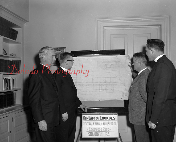 (October 1957) Officials looking over blue prints for Our Lady of Lourdes in late 1957.