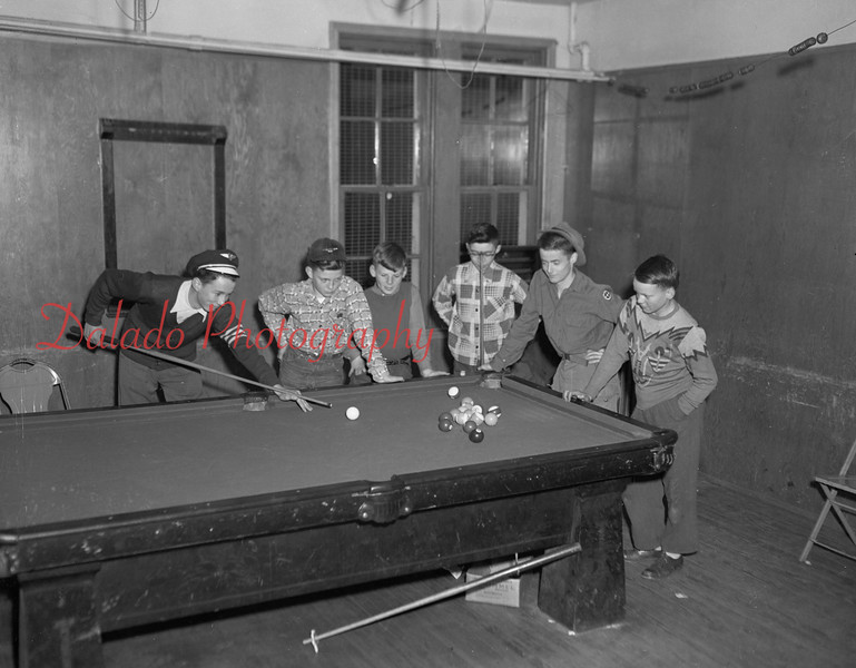 (03.11.54) Ronald McElwee very intent upon making a combination shot in a vary close game at St. Joseph's recreation hall, Locust Gap, watched by Robert Klinger, Edward Boblick, Joe McGinn, Joe Maron and Larry Honicker.