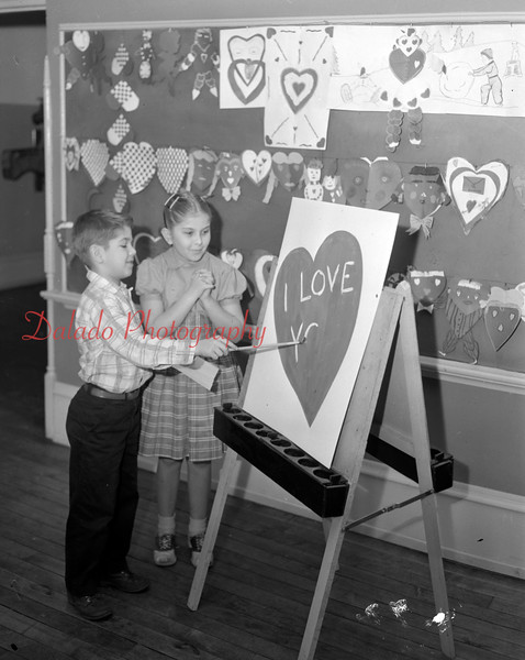 """(Feb. 57) Spelling out the message of Valentine Day is David Long, as Diana James waits anxiously until he finishes that one word, """"You,"""" at the Grant Grade school."""