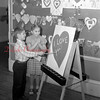 "(Feb. 57) Spelling out the message of Valentine Day is David Long, as Diana James waits anxiously until he finishes that one word, ""You,"" at the Grant Grade school."