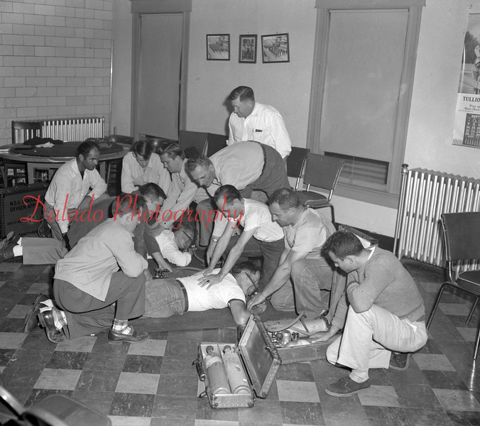 (10.05.52) Kulpmont firemen witness a demonstration of artificial respiration and the use of modern first-aid equipment. Shown are, clockwise, from left, J. Lukawitski, Sam Pitelto, Albert Fodor, Robert Pastal, Stanley Rutkowski, Joseph Lahnstein, Nick Avellino, Mike Benedetto and Nick Benedetto. On the floor is Joseph Kaszleger and David Coneleski. Looking on is Edward Murdock.