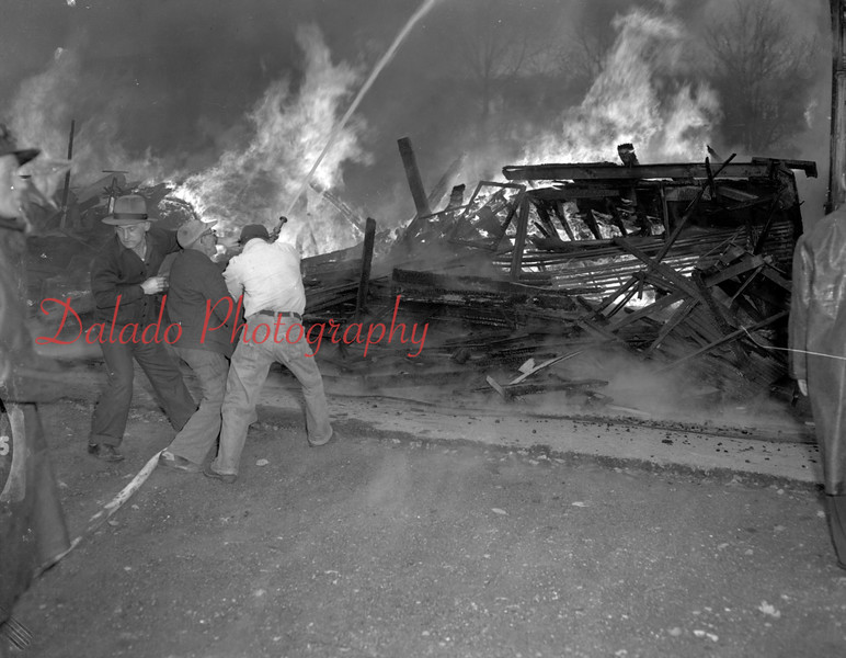 """(12.13.52) Coal Township firemen were handicapped in bringing under control this raging fire that struck the auto body shop and homes of Edwards and Earl Dornbach at around 2:45p.m. Fire officials said neighboring homes were """"red hot"""" when they arrived. Rufas Yost, of 1532 Walnut Street, said clothing hanging on a washline was burned."""