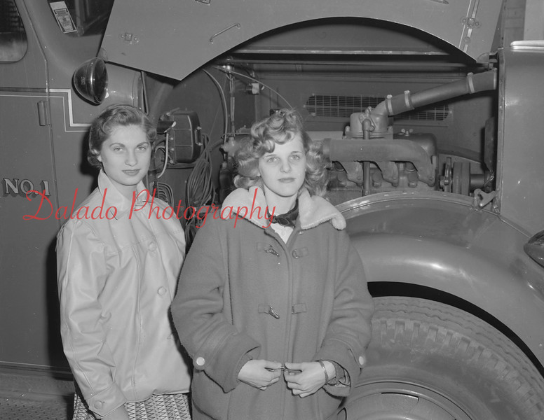 Ladies in front of a fire truck.