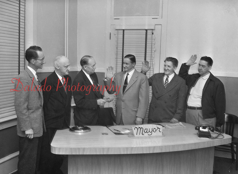 (01.03.57) Mayor Lester Weller administers the oath of office to the city's newest fire chiefs. Being sworn in are William Bashore, chief; Alphonse Letcavage, first assistant; and Thomas Walsh, second assistant. Also shown are Claude Kehler, director of public safety and Walter Romanoskie, retiring fire chief.