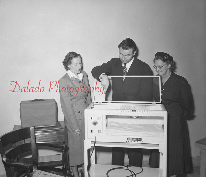 (12.06.51) A portable incubator for infants was presented to Shamokin Hospital by the Ladies Auxiliary. Pictured are John Colby, explaining the unit, Mrs. Chester Lark, center, and Mrs. Leonard Smith, members of the auxiliary.