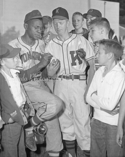 """(06.15.55) Leroy """"Satchel"""" Paige signs autographs for youthful admirers after pitching three scoreless innings against Krebs Electric at the Tharptown baseball diamond in June 1955. At the age of 42, the right-handed pitcher became the first Black person to play in the American League, and was elected into the National Baseball Hall of fame in 1971."""