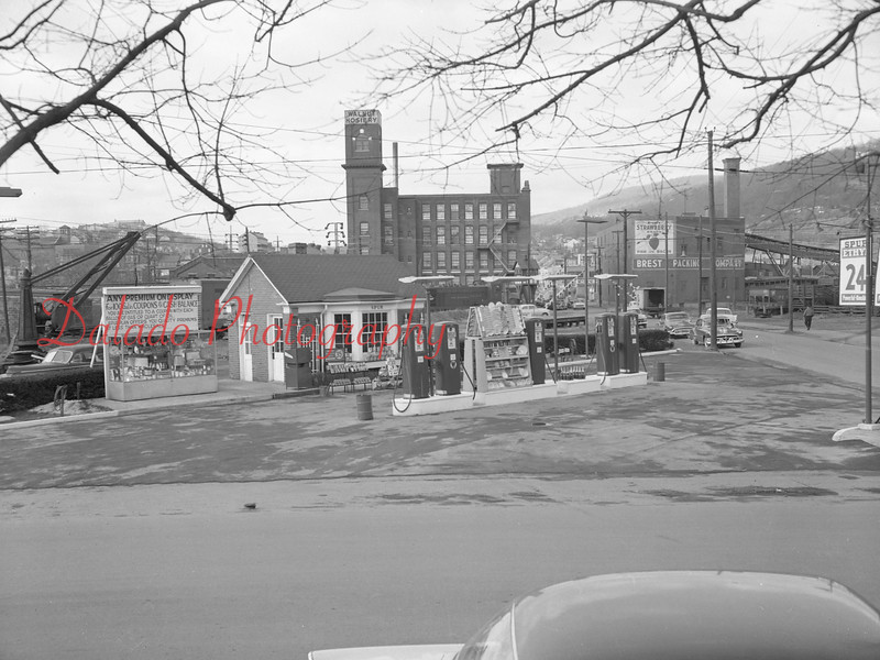 """(1956) Spurr Gas Station- In the distance are Walnut Hosiery, left, (later Walnut Towers Inn and the Coal Hole) and Brest Packing (later Kreisl Brothers Inc. and Croninger Packing Co.), right. On April 28, 1962, Kreisl, a meat packing plant, closed permanently. Henry Kreisl, owner who employed 50 people, said that he """"could not meet union demands"""" during negotiations for a new contract. The plant had operated since 1939, when the Kreisl brothers acquired it from Harry Brest. The building was lastly occupied by Croninger. The structure was purchased by John Luckens, who then demolished it on Jan. 22, 1974, for parking for his new motel, Walnut Towers. Luckens and eight other people died in an arson fire at the motel on Jan. 2, 1977. <a href=""""http://www.daladophotography.com/The-Thomas-Collection/Old-Fire-Fighting/3333623_xc79SC#!i=1321295761&k=CfXnPZn"""">http://www.daladophotography.com/The-Thomas-Collection/Old-Fire-Fighting/3333623_xc79SC#!i=1321295761&k=CfXnPZn</a>"""