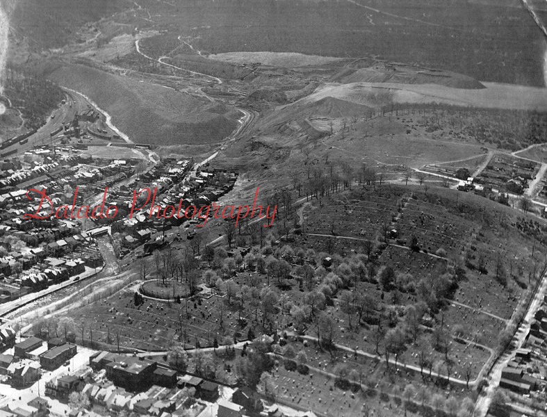 """(1941) An aerial shot from above Shamokin. This is looking southeast towards Big Mountain. In the upper-left hand corner is the Philadelphia & Reading Railroad Company (Reading Company) Shamokin yard facility. The locomotives were turned on the """"Y"""" track by using the mine spur that runs behind the coal bank and the main line north and south in the photo."""