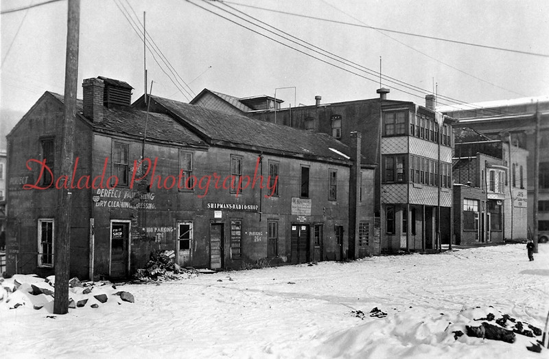 "Station Row along what would eventually become Water Street near Liberty Street. Thomas Studio is the building in the middle. The business sign reads, ""Shipman's Radio Shop."""