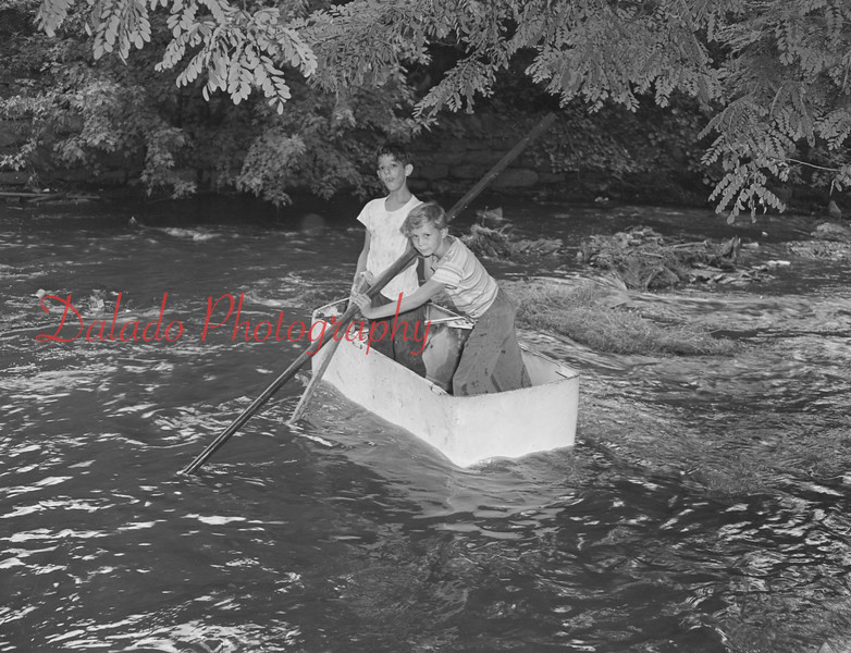 "(Sept. 1959) Richard Bixler and John Berry navigate the Shamokin Creek behind the Friendship Fire Co. on the ""USS Refrigerator."""