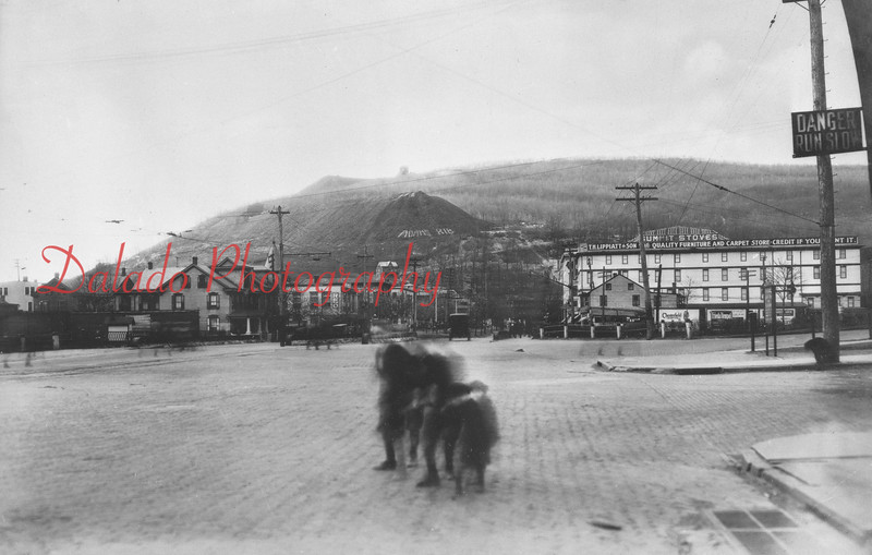 """Market and Arch streets. The white building in the background is T.M. Lipplatt & Son, a furniture and carpet store. On the Glen Burn Bank the words """"Adams Rib"""" can be seen."""