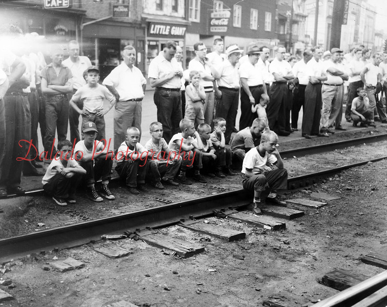 (7.1955) Not sure what everyone is watching, but supposedly they are watching it at the corner of Shamokin and Independence streets.