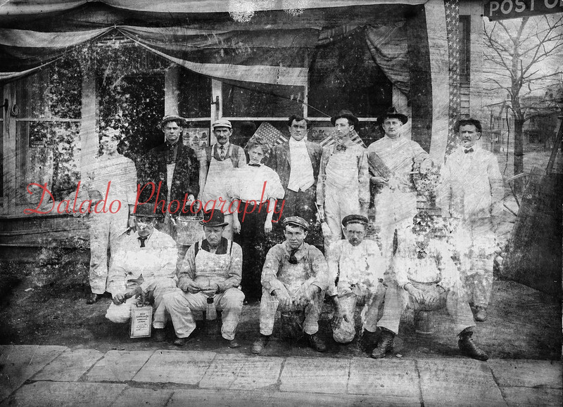 "J.W. Maus Paint Store and U.S. Post Office on the corner of Chestnut and Second streets- This photo is in pretty bad shape, but I can tell the men are painters. The man sitting at far left is sitting on a can of varnish, while several others hold buckets and small brooms. Oddly, there is a woman in the center. Even though this photo says taken ""about 1890,"" the American flag has 48 stars. This would mean it was taken some time after Feb 14, 1912, the day Arizona entered statehood and became the 48th state."